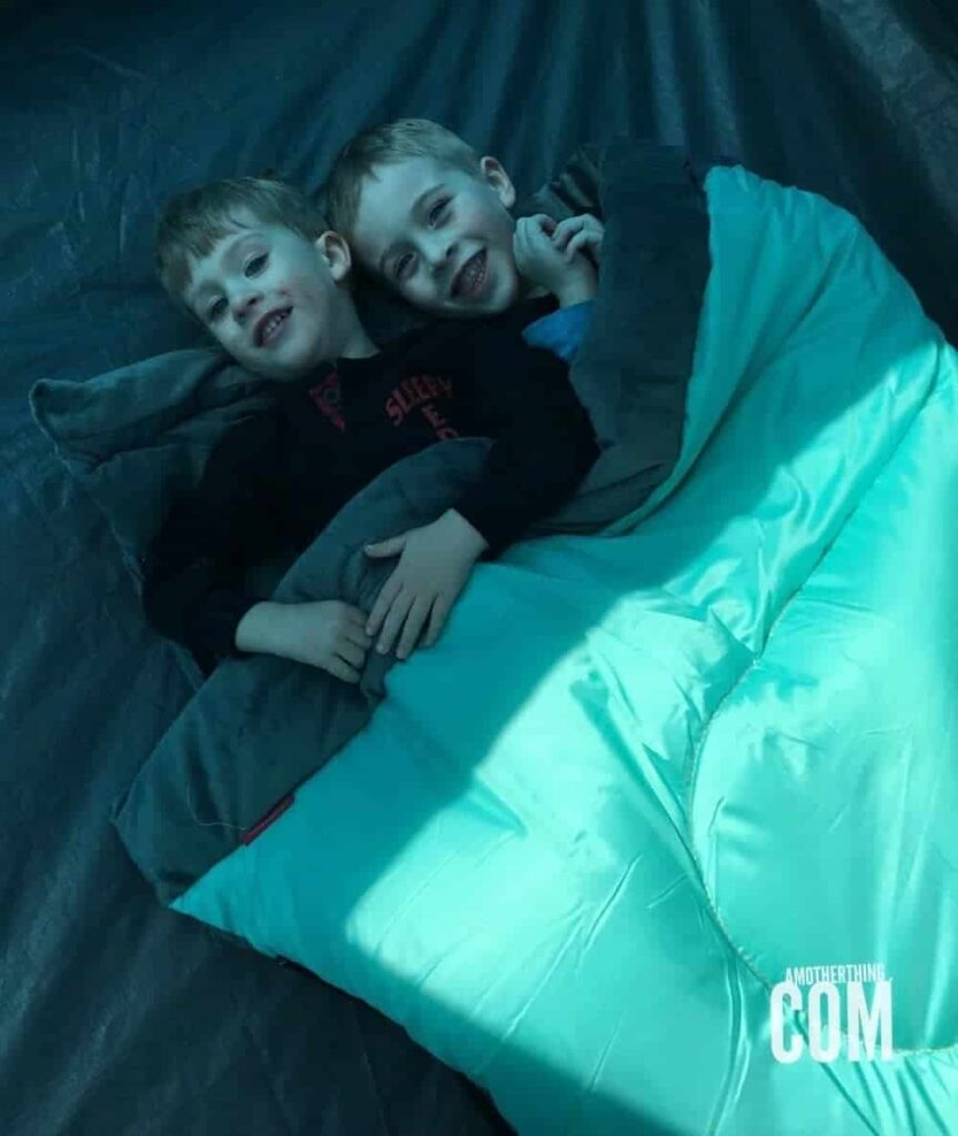 two young boys sharing a sleeping bag