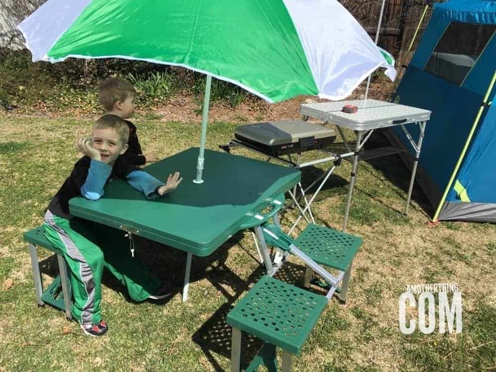 children sitting at a small camping picnic table