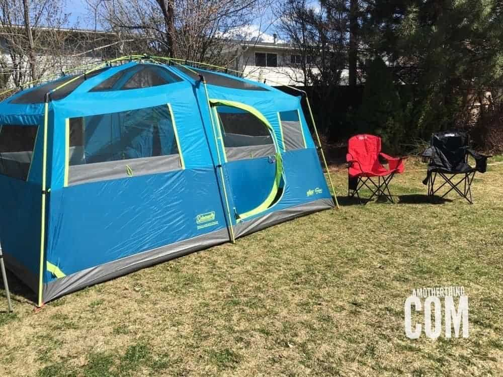 a large blue tent set up in the back yard with two camping chairs