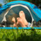 A couple pairs of feet extend out from a blue tent